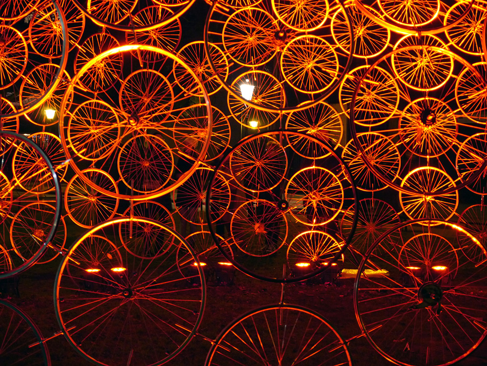"""300 bicycle rims glow like orange slices in """"Re(bi)cycle"""" by Russian-born architect Vasili Popov. But there's a catch – the dome won't glow without the work of its spectators, who must power this impressive structure via a water pump. Amsterdam is known for its throngs of cyclists – for many they form the heart and soul of the city. Credit: Nicola Brown"""