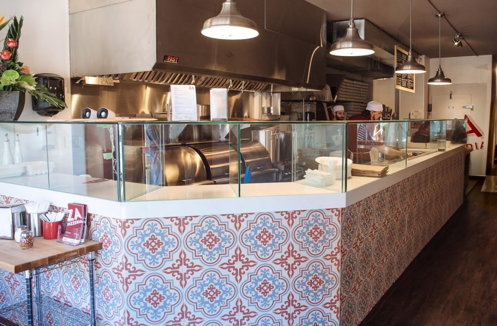 A full-length counter and red room accents welcome guests to Za Pizzeria.